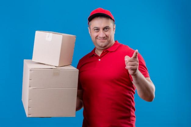 Liefermann, der rote uniform und kappe hält, die pappkartons hält, die auf etwas mit zeigefinger zeigen, der zuversichtlich und glücklich über blaue wand lächelt