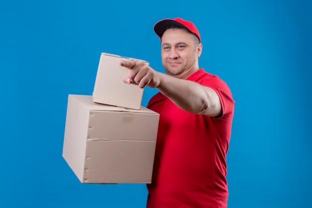 Liefermann, der rote uniform und kappe hält, die pappkartons hält, die beiseite schauen und auf etwas mit zeigefinger zeigen