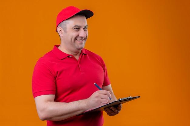 Liefermann, der rote uniform und kappe hält, die zwischenablage hält, die beiseite positiv und glücklich schaut, etwas schreibend über orange wand