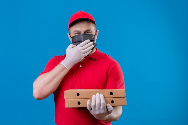 Liefermann, der rote uniform und kappe in der gesichtsschutzmaske trägt, die pizzaschachteln hält, die überrascht den mund mit der hand über der blauen wand bedeckend suchen