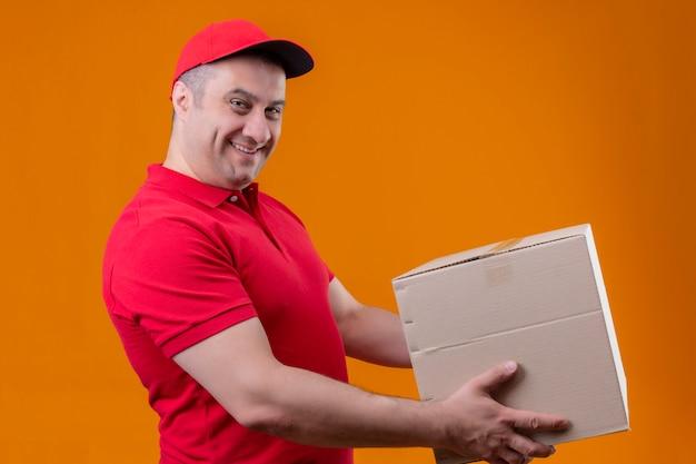 Liefermann, der rote uniform und kappe trägt, die einem kunden pappkarton mit selbstbewusstem lächeln auf isoliertem orange steht