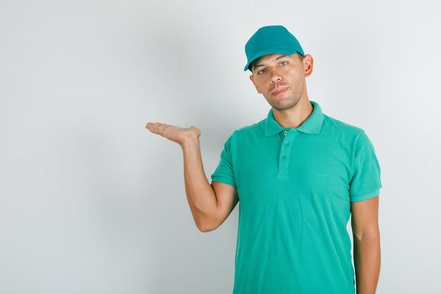 Liefermann hält geöffnete hand im grünen t-shirt und in der kappe