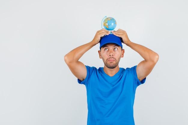 Liefermann im blauen t-shirt, kappe, die globus auf kopf hält und lustig schaut