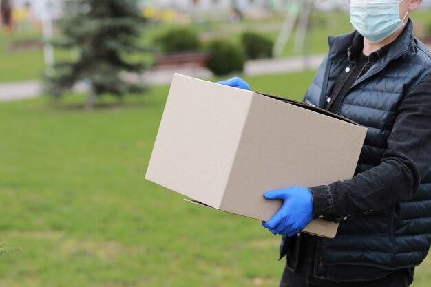 Liefermann im gesicht medizinische maskenhandschuhe halten leere pappschachtel im freien