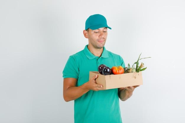Liefermann im grünen t-shirt und in der kappe, die gemüse in der schachtel halten und fröhlich schauen