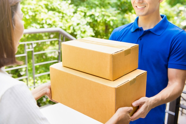 Liefermann in blauer uniform, der einer frau paketboxen übergibt
