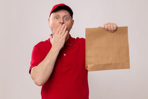 Liefermann in der roten uniform und in der kappe, die papierpaket hält, das kamera betrachtet, die shocekd bedeckt mund, mit hand steht über weißem hintergrund