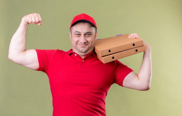 Liefermann in der roten uniform und in der kappe, die pizzaschachteln hält, die bizeps auf seiner hand zeigen, zuversichtlich lächelnd, gewinnerkonzept stehend auf grün