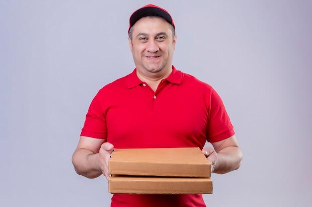 Liefermann in der roten uniform und in der kappe, die pizzaschachteln halten, die positiv und glücklich lächelnd freundlich stehen, stehen über lokalisiertem weißem raum