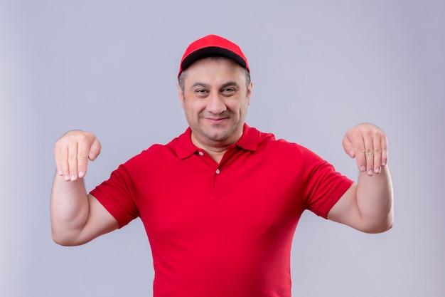 Liefermann in der roten uniform und in der kappe gestikulierend mit hand lächelndem körpersprachenkonzept stehend