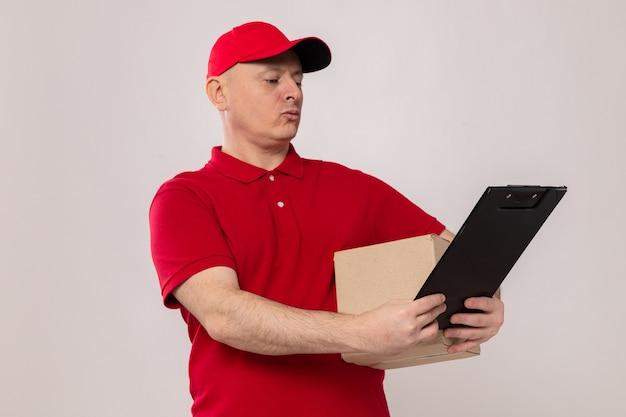 Liefermann in roter uniform und mütze mit karton und klemmbrett, der es mit ernstem gesicht auf weißem hintergrund betrachtet