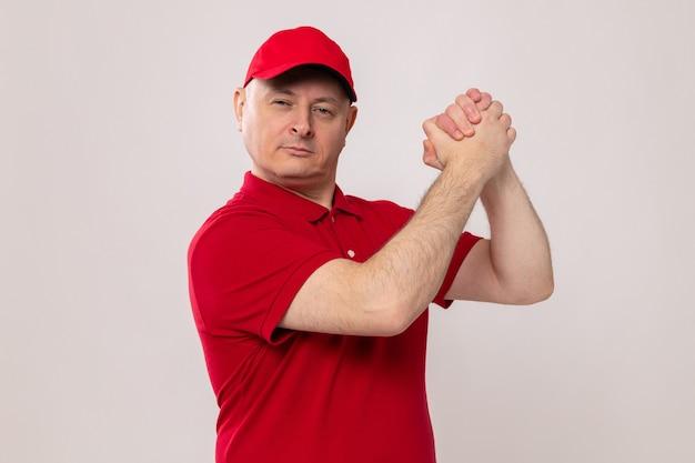 Liefermann in roter uniform und mütze mit selbstbewusstem ausdruck, der die hände zusammenhält und teamwork-geste macht