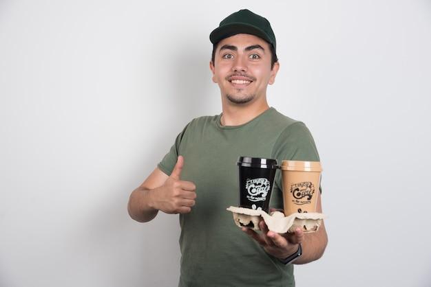 Liefermann mit tassen des kaffees, der daumen auf weißem hintergrund macht.