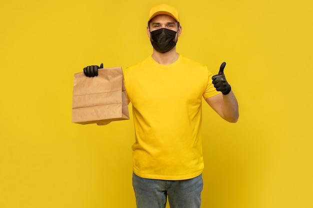 Liefermann mitarbeiter in gelben kappe t-shirt uniform maske handschuh halten handwerk papierpaket mit lebensmittel isoliert