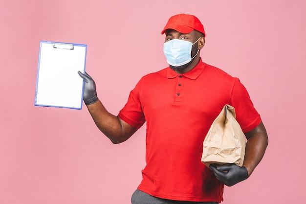 Liefermann mitarbeiter in roter kappe leer t-shirt uniform gesichtsmaske handschuhe halten leere pappschachtel.