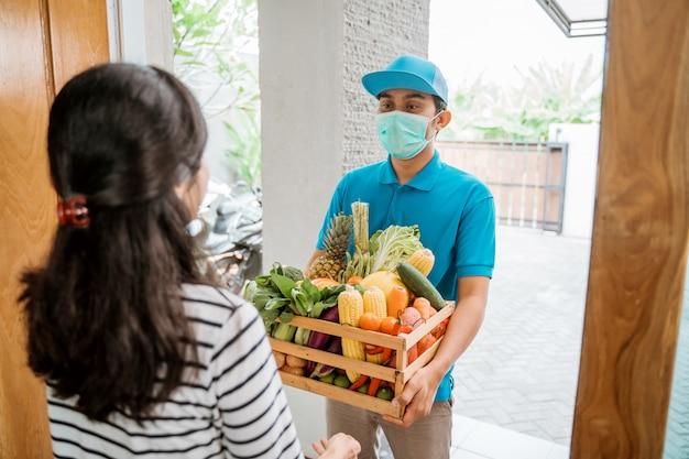 Liefermann tragen gesichtsmaske während der lieferung von lebensmitteln