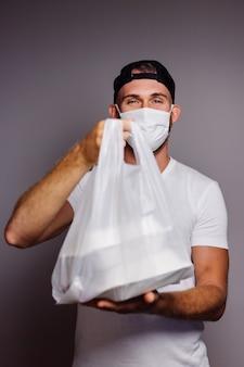Liefern sie mann, der plastiktüte mit essen im türweg hält