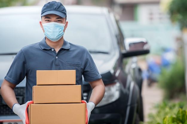 Lieferpersonal mit papierboxen. tragen sie medizinische handschuhe und masken, um covid-19 zu schützen