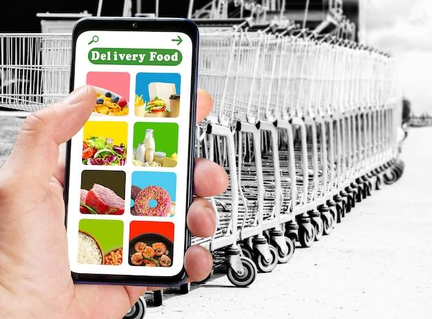 Lieferservice-app auf dem telefonbildschirm auf leeren einkaufswagen auf parkplatzhintergrund