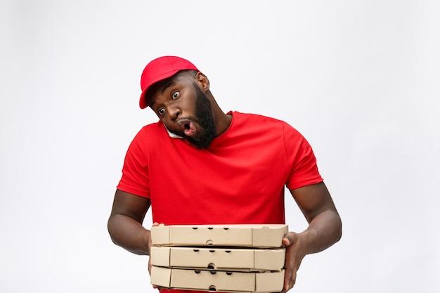 Lieferservice: hübscher afrikanischer pizzaboten, der mit schockierendem gesichtsausdruck mit handy spricht.