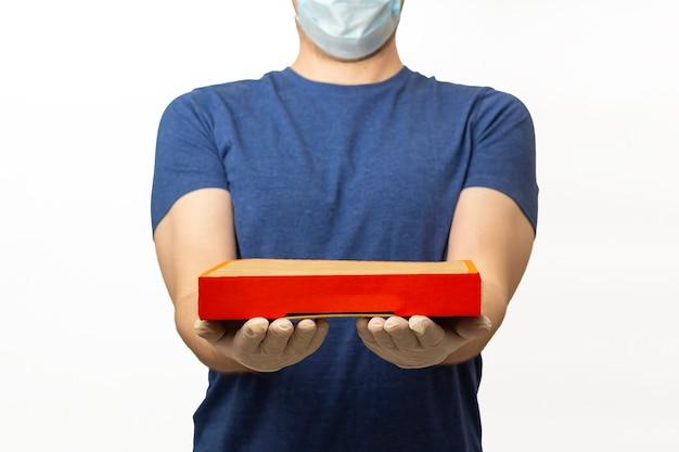 Lieferservice während der quarantäne. lieferbote in gummihandschuhen und schützender medizinischer gesichtsmaske hält box für pizza. bleiben sie zu hause und kaufen sie online bei ausbruch des coronavirus ein.