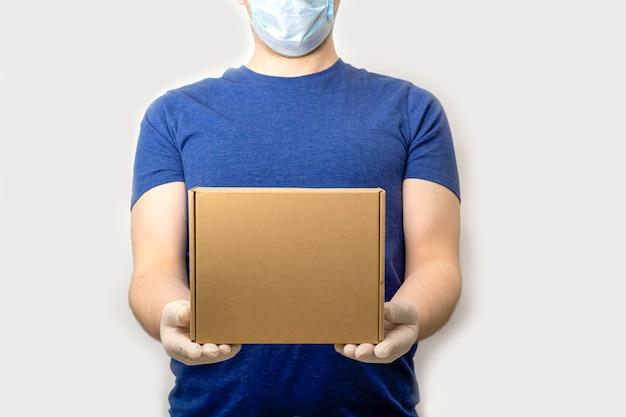 Lieferservice während der quarantäne. lieferbote in gummihandschuhen und schützender medizinischer gesichtsmaske hält pappkarton.