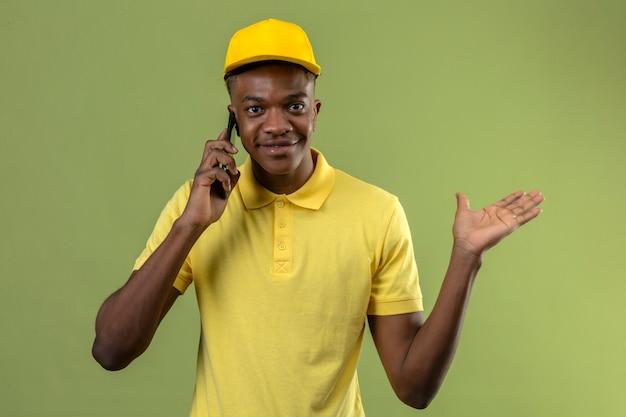 Lieferung afroamerikaner mann im gelben poloshirt und in der kappe, die auf handy sprechen, freundlich lächelnd und präsentierend und zeigend mit handfläche stehend auf lokalisiertem grün