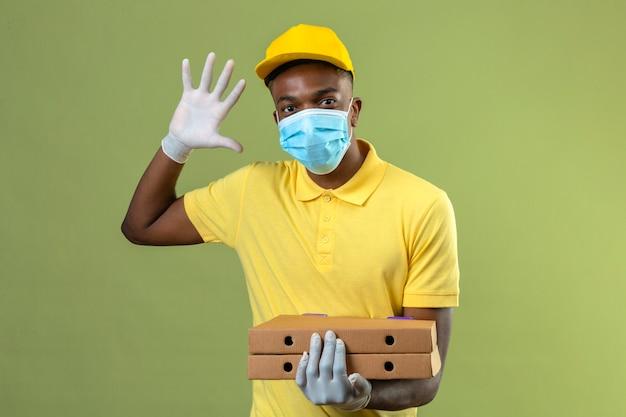 Lieferung afroamerikaner mann in gelbem poloshirt und kappe, die medizinische schutzmaske hält, die pizzaschachteln zeigt nummer fünf mit offener hand steht auf grün