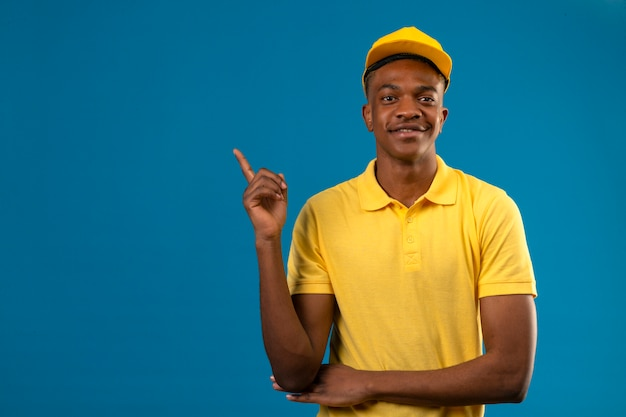 Lieferung afroamerikaner mann in gelbem poloshirt und kappe mit sicherem lächeln, das mit finger zur seite zeigt, die auf lokalisiertem blau steht