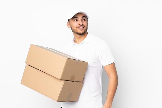 Lieferung arabischer mann auf blauer wand lachend und aufblickend