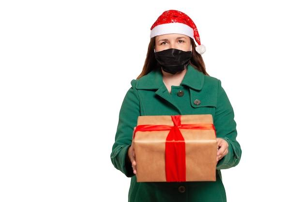 Lieferung eines weihnachtsgeschenks nach hause mit medizinischer maske. geschenklieferung für weihnachten lokalisiert auf weiß