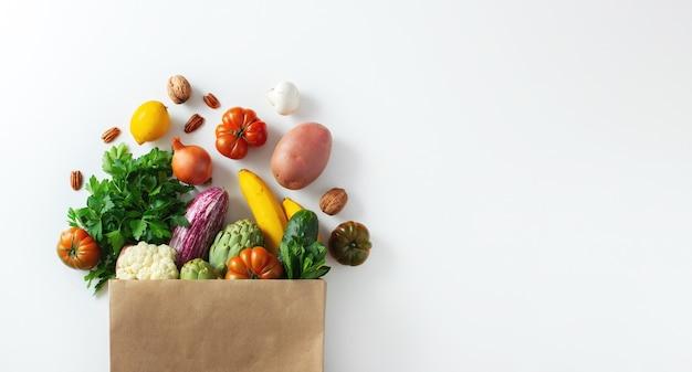 Lieferung gesundes veganes vegetarisches essen in papiertütengemüse und -früchten auf weiß. einkaufen lebensmittelsupermarkt und sauberes veganes esskonzept.