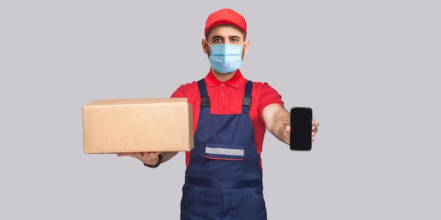 Lieferung in quarantäne. das ist für dich! junger mann mit chirurgischer medizinischer maske in blauer uniform und rotem t-shirt stehend, hält karton und zeigt smartphone-display auf grauem hintergrund.