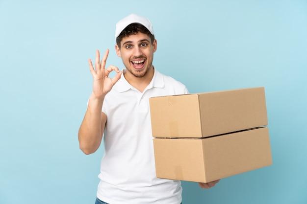 Lieferung kaukasischer mann auf blauer wand, die ein ok zeichen mit den fingern zeigt