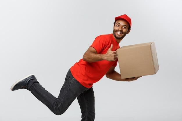 Lieferung konzept - handsome african american lieferung mann eile läuft für die bereitstellung eines pakets für kunden. isoliert auf grau studio hintergrund. text kopieren