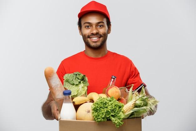 Lieferung konzept - handsome african american lieferung mann mit paket box von lebensmitteln lebensmittel und getränk aus dem laden. isoliert auf grau studio hintergrund. text kopieren