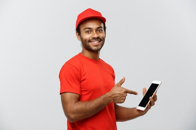 Lieferung konzept - porträt von handsome african american lieferung mann oder kurier mit box zeigt tablette auf sie, um die bestellung zu überprüfen. isoliert auf grau studio hintergrund. text kopieren