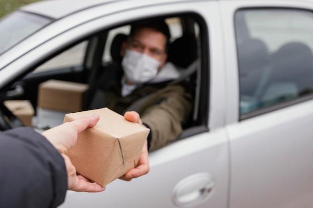Lieferung männlich mit maske und paketen