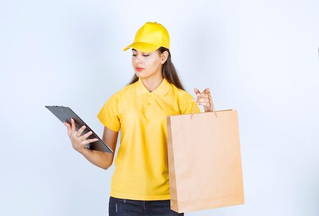 Lieferung mitarbeiter frau in gelber mütze halten in der hand braunes kraftpapier und zwischenablage.