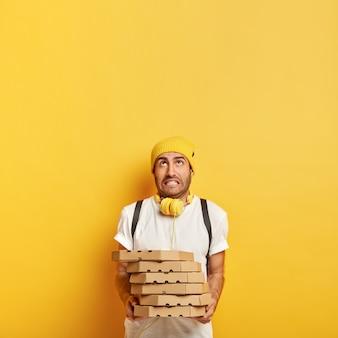Lieferung nach hause von der pizzeria. müdigkeit mann gekleidet in freizeitkleidung, hält stapel von pappkartons, posiert mit lebensmittelbestellung. der junge pizzamann arbeitet als kurierhändler und konzentriert sich oben auf den kopierraum