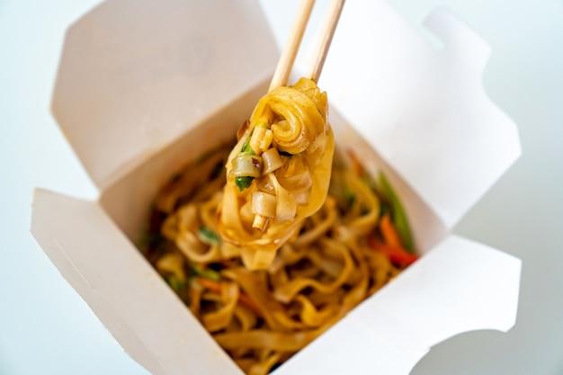 Lieferung von asiatischen fertiggerichten. nudeln mit gemüse und meeresfrüchten in einer weißen schachtel und sushi-sticks. köstliches abendessen. essen bestellen telefonisch oder online.