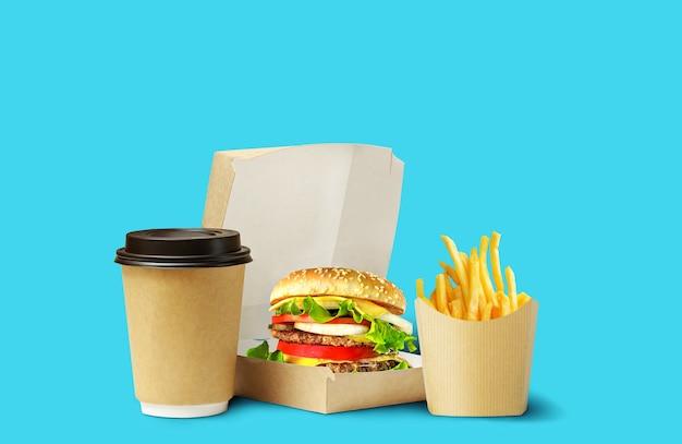 Lieferung von fast-food-mittagessen. leckerer hamburger, pommes und kaffee in kartonverpackung auf blauem hintergrund.