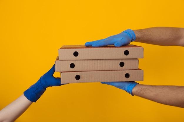 Lieferung von lebensmitteln bei pandemie. mann, der der frau pizzaschachteln gibt.