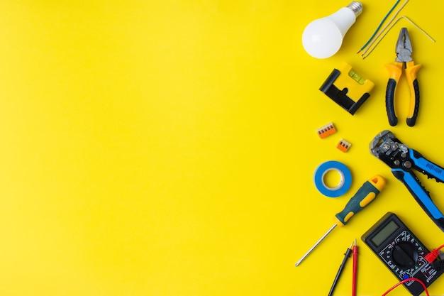 Lieferungen verschiedener elektriker auf gelbem hintergrund. hintergrund der professionellen elektrikerwerkzeuge
