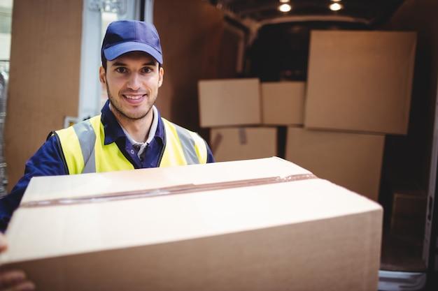 Lieferungsfahrer, der an der kamera durch seinen packwagen hält paket außerhalb des lagers lächelt