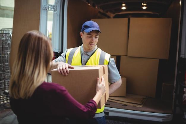 Lieferungsfahrer, der dem kunden paket außerhalb des packwagens im lager übergibt