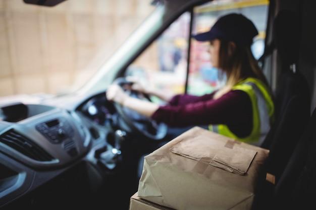 Lieferungsfahrer, der packwagen mit paketen auf sitz außerhalb des lagers fährt