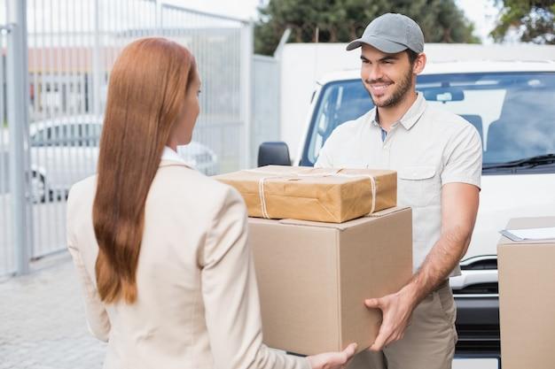Lieferungsfahrer, der pakete zum glücklichen kunden führt
