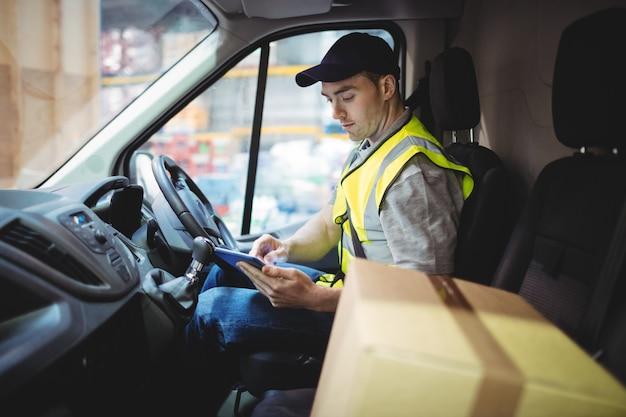 Lieferungsfahrer, der tablette im packwagen mit paketen auf sitz außerhalb des lagers verwendet