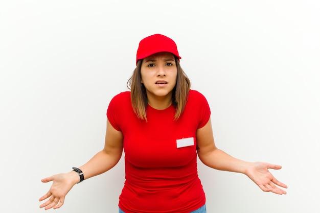 Lieferungsfrau, die ahnungslos und verwirrt sich fühlt und keine ahnung hat, absolut verwirrt mit einem stummen oder dummen blick gegen weißen hintergrund